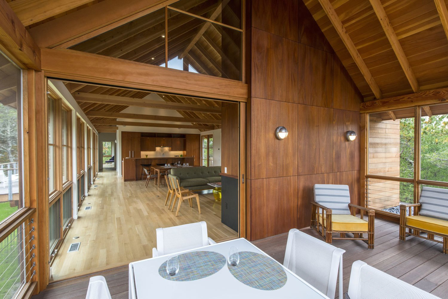 Varying types of wood make up the home's interior: white oak planks for the floor, solid mahogany for the cabinets, and fir for the ceilings, beams, columns, and trim.  Photo 1 of 10 in 10 Enclosed Porches That Are Put to Good Use from A Modern Take on the Gabled Cabin in Cape Cod