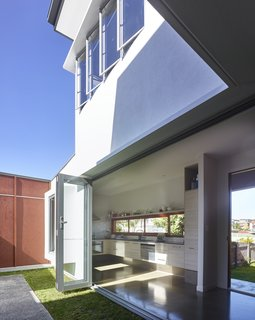 By opening doors and windows on opposite sides of the house and on upper and lower floors, air can easily circulate through this home.