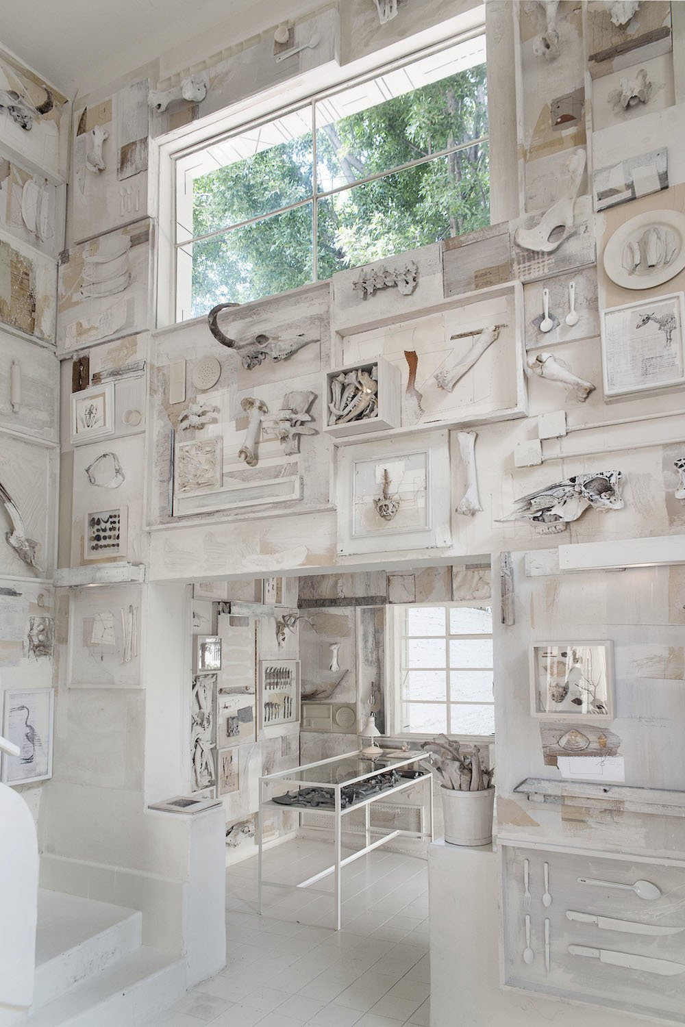 """""""The pieces told us what they wanted to do on the wall,"""" Cadena says. The menagerie of bones, including pieces from boar, turtles, and even a whale's vertebrae, are deliberately off-white, so it doesn't come across as too pure. The tables and chairs are separated from the walls, so diners aren't too distracted by the details of the elaborate, hand-made murals, which include silverware, serving utensils, and pieces from books.  Photo 4 of 9 in 10,000 Bones Cover the Walls of this Mexico Restaurant"""