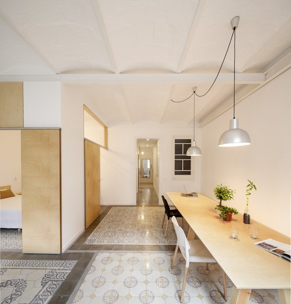 A 1930s apartment in Barcelona was renovated by Adrian Elizalde, where the architect removed interior walls and an old plaster ceiling, revealing original masonry arch ceiling construction. Covered with a coat of white paint, the ceiling provides subtle texture and pattern to the smooth and neutral white and plywood walls.