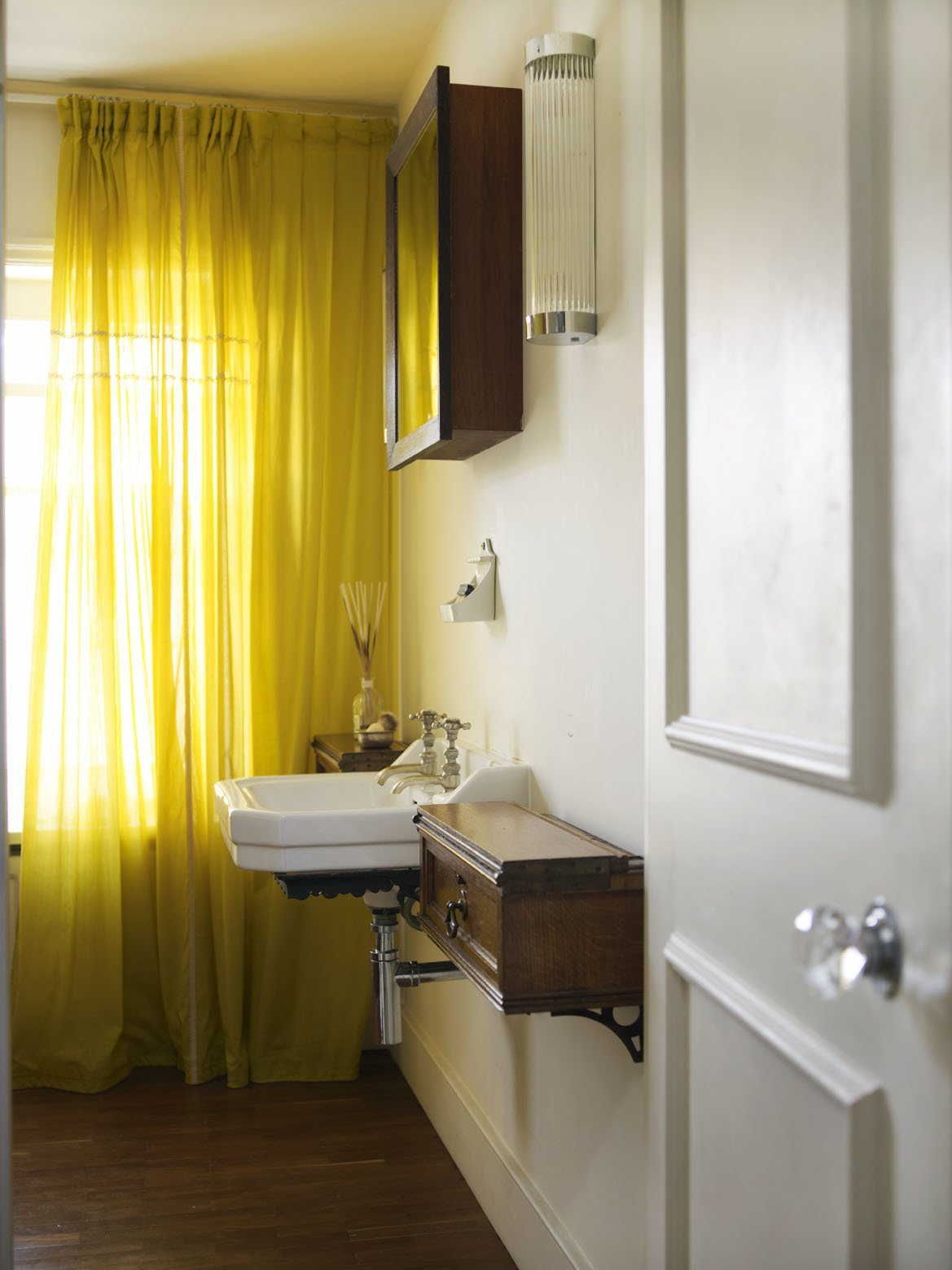 The cupboards of this bathroom are faced in panels of heavily aged leather, originally used on shelves in The British Library.  Photo 9 of 12 in A Gracious London Terrace House Is Reborn with Salvaged Materials