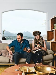 """In the living room of their Vancouver home, Omer Arbel and Aileen Bryant sit on a Coronado sofa by Afra and Tobia Scarpa for B&B Italia. They are joined by their Weimaraner, Bowie, boa constrictor, Picasso, and milk snake, Legs.<br><br>""""I have a casual approach to prototyping that involves our day-to-day life. I am always tinkering, and I have lots of transformers to run electricity through things, but Aileen lives with me now, so I have to be respectful. Before she moved in it was like a total madhouse; now I can't pour concrete in the kitchen. It is a collaboration in a sentimental sense. This work is my life, and the objects are my objects, but how they are arranged and the flow of each room are something we've created together here."""""""