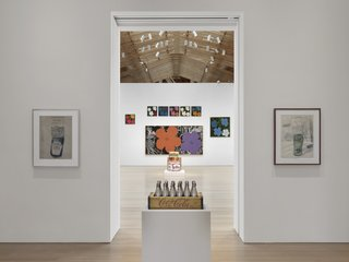 From Warhol's famous hyper-color prints of hibiscus flowers (background), to his little known (unreleased) perfume collaboration (contained within the silver Coke bottles in front).<br><br>Credit Stefan Altenburger, Courtesy The Brant Foundation