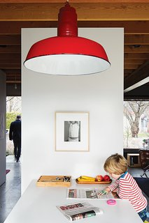 This bright red vintage pendant is perfectly centered over the dining room table, rather than to the center of the room.