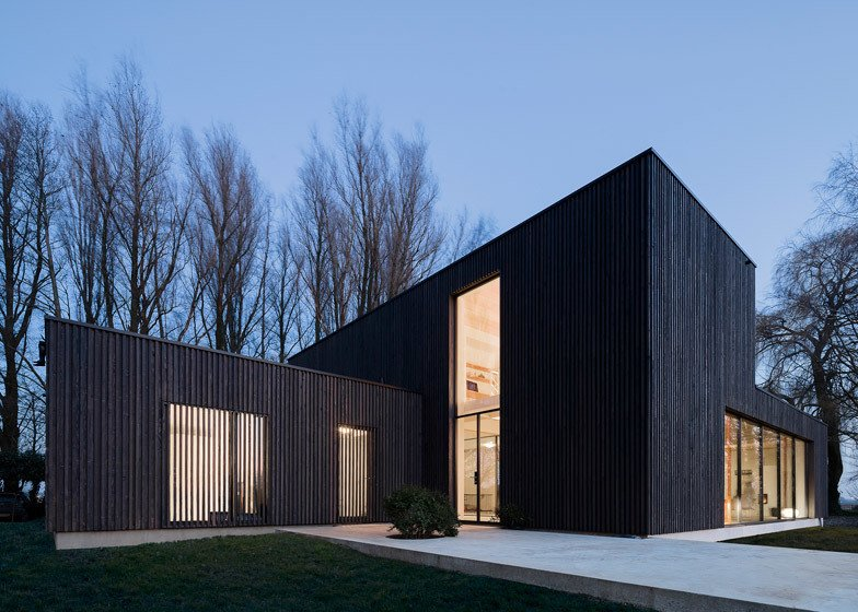 """We wanted the wood to appear as natural as possible, so leaving the larch untreated was the first choice,"" Bas explained. But the shape of the house would make the wood turn gray unevenly, so they blackened the larch. ""The clients were excited with the dark color as it helps the house blend into the trees. They didn't want the anything excessive or showy."" But blackened timber comes with its own challenges. Since it absorbs more heat, a larger air cavity was built behind the wood to keep it cool.  Photo 2 of 6 in This Blackened Timber House Triumphantly Emerges After a Fire"