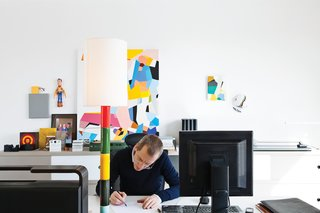 Interior architect and resident Renaud de Poorter works in his second-floor office at a pair of Joyn tables by the Bouroullec brothers and an Ypsilon office chair by Mario Bellini for Vitra.