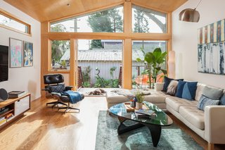 Remodeled by resident and interior decorator Jill McCoy and her husband David Hassall with the help of architect Paul Molina, the open-plan living space opens to a small outdoor area. French doors and a wall of windows bring in light. An Eames lounge chair and a Noguchi table add a modern sensibility.