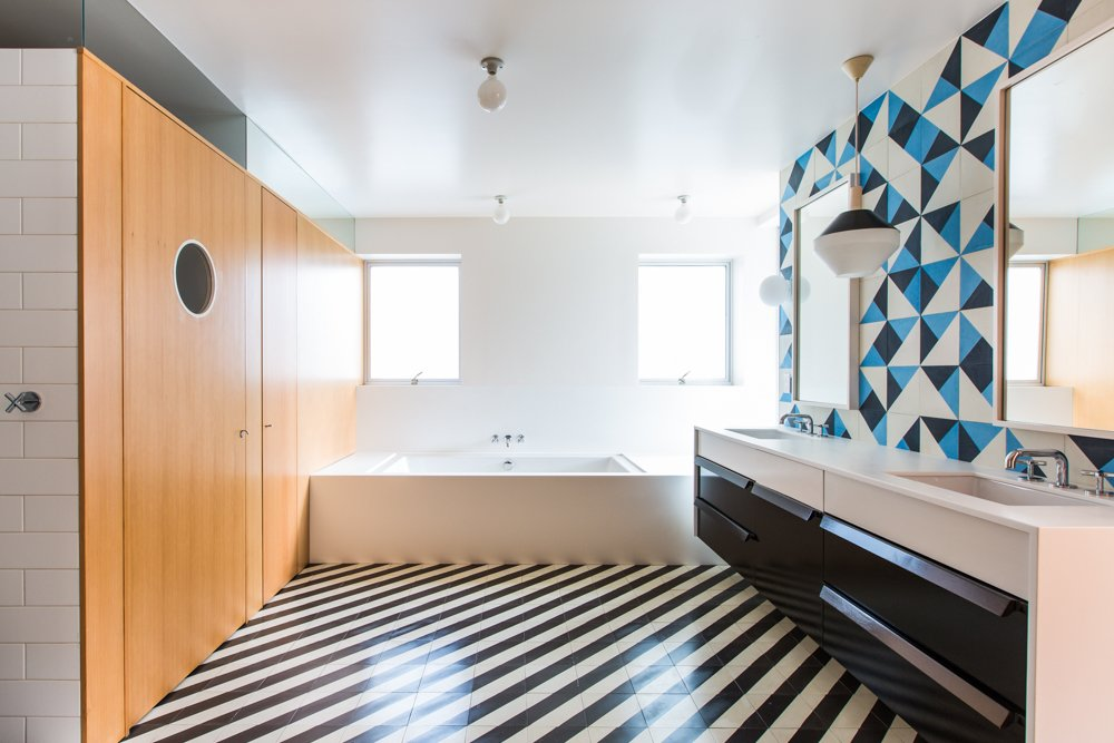 Bath Room, Ceramic Tile Floor, Undermount Sink, Soaking Tub, Pendant Lighting, Ceiling Lighting, and Ceramic Tile Wall Architect Barbara Bestor added a striped floor of Santander Granada Tile, Douglas Fir cladding, and Granada Serengeti tile flipped to create a one-of-a-kind pattern on the wall.  Photo 13 of 20 in 20 Bathrooms With Transformative Tiles from A Bright, Geometric Bathroom Renovation in Los Angeles