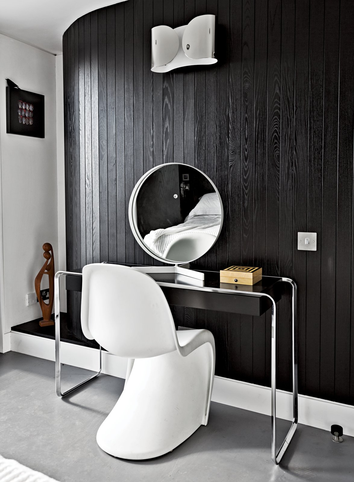 "Bedroom, Wall Lighting, and Concrete Floor Near the room's curving wall, a Verner Panton chair joins a K2 B console table by Tecta, topped by a vintage mirror by Robert Welch. The wall light is from Flos. ""If I had more space, I'd just fill it with more stuff,"" says Pearce.  Photo 3 of 7 in An Elevated Deckhouse in England"