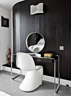 "Near the room's curving wall, a Verner Panton chair joins a K2 B console table by Tecta, topped by a vintage mirror by Robert Welch. The wall light is from Flos. ""If I had more space, I'd just fill it with more stuff,"" says Pearce. The black-and-white palette echoes the home's exterior."