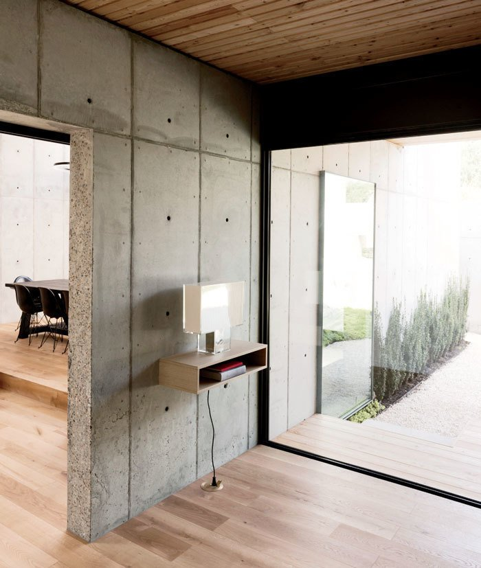 Windows In the entryway, a Tati lamp by Ferruccio Laviani for Kartell sits on a shelf Christopher made from kitchen cabinetry scraps.  Photo 7 of 17 in A Texas Couple Builds Their Cast-In-Place Concrete Dream Home