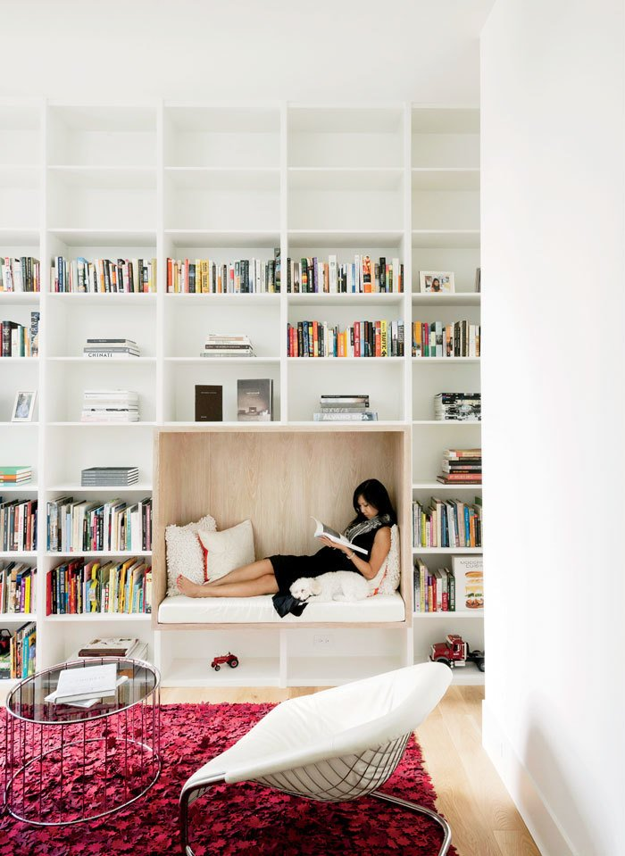 Living Room, Coffee Tables, Chair, Bench, Light Hardwood Floor, and Rug Floor Awaiting the birth of the couple's son, Vivi relaxes in a built-in reading nook in the library.  Photo 9 of 17 in A Texas Couple Builds Their Cast-In-Place Concrete Dream Home