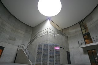 Among the artwork on display is Bruce Nauman's 1984 100 Live and Die. Mounted on four metal monoliths, the neon's flickering glow is surrounded by Ando's concrete walls and skylight above. Photo Courtesy 準建築人手札網站 Forgemind ArchiMedia via flikr.