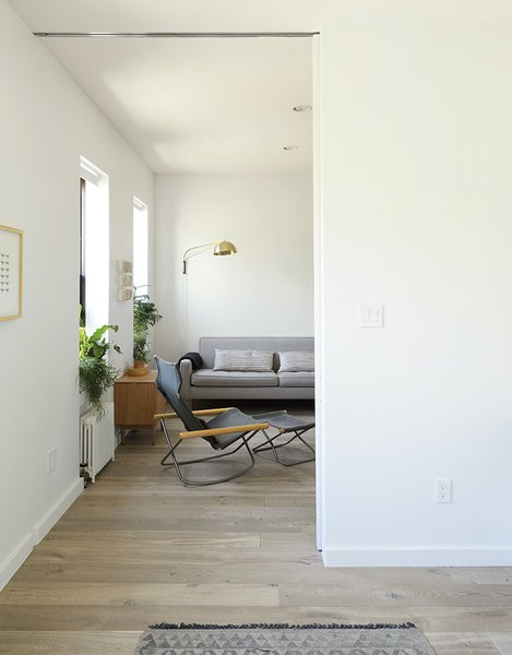 Takeshi Nii's Ny chair is paired with a Reese sofa and cherry Grove nightstand from Room & Board in the living room.  Photo 10 of 14 in How One Family of Three Does It All in 675 Square Feet