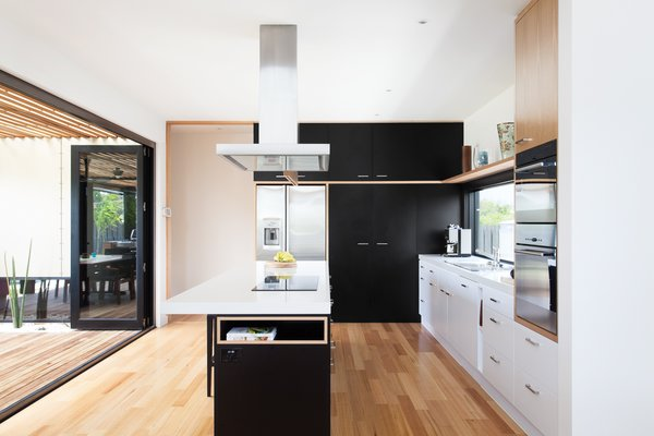 In the kitchen, an island countertop serves as a mixed-use area for cooking, storage, and seating for up to five people. The room opens up to an outdoor dining area.