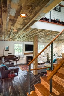 "The staircase works as a visual transition from the cozy first level to the more modern second floor. When standing downstairs, the staircase pulls away from the dark anchoring floorboards with angled steel beams, stainless steel cables, and wood caps. ""It's thin and light so that it wouldn't impede connection to the first floor,"" says Michael. ""It's meant to be pretty modern, but the wood cap softens the look a little, and makes the experience of touching the railing softer."""