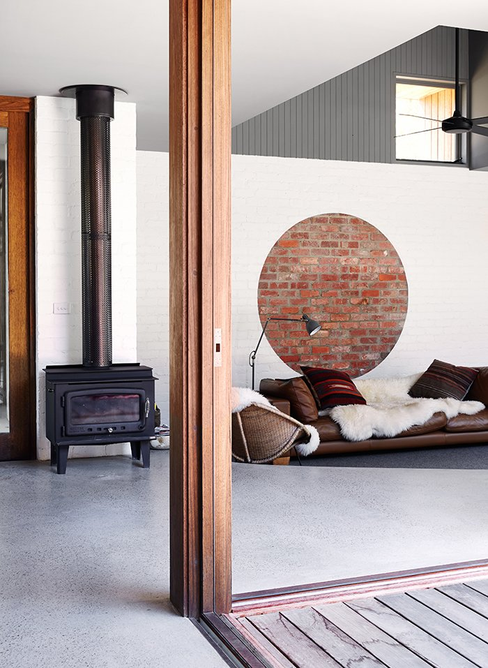 """Living Room, Wood Burning Fireplace, Sofa, and Floor Lighting """"The idea is not needing too much furniture for the house to work,"""" Nolan says. The sofa is from Melbourne's Jardan, the floor lamp is Ikea, and the rocking chair is vintage. In winter, the family often gathers around the Nectre wood stove, the sole heating element in the house.  Photo 4 of 11 in Simplicity Rules at this Family Beach House Designed to Double as a Rental"""