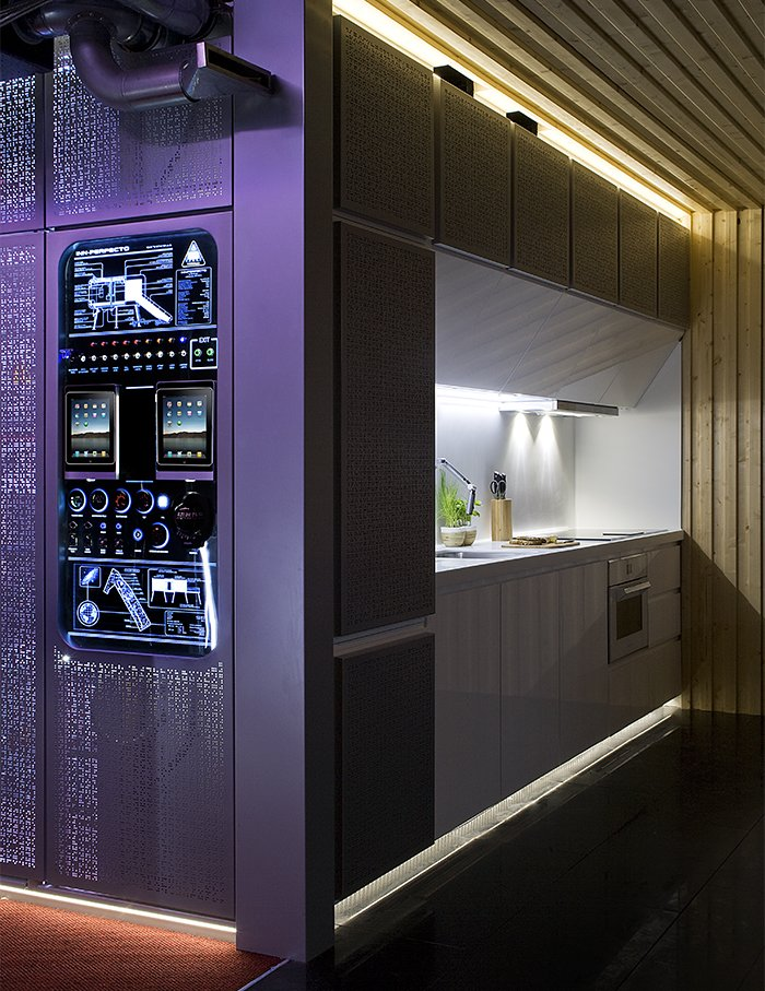 """Kitchen, Range, Range Hood, Accent Lighting, and Quartzite Counter NOEM integrated the mechanical systems behind a purple screen for users to access. This """"hub"""" is the first thing visible upon opening the front door.  Photo 5 of 9 in This Futuristic Prefab in Spain Has All the High-Tech Gizmos of a Spaceship"""
