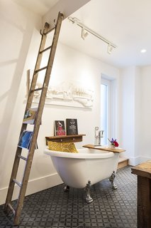 A new clawfoot tub sits next to an old wooden ladder that serves as a towel and magazine rack.
