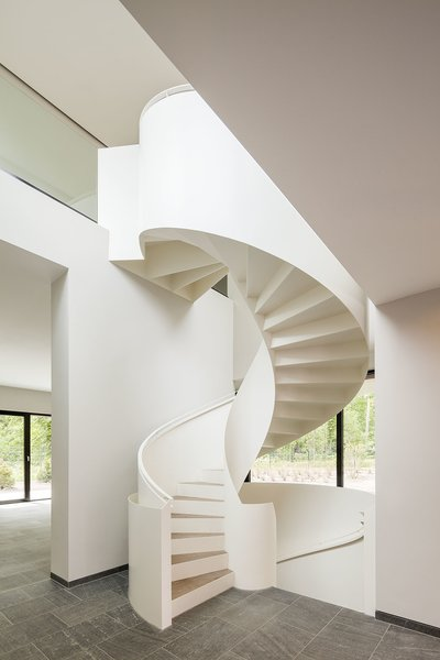 A sculptural white steel spiral staircase with wooden treads connects a lower level to an upper cantilevered level in this home near Potsdam, Germany, that was designed by Nps Tchoban Voss. The slim profile of the steel contrasts with the undulating curves of the powder-coated steel railing.