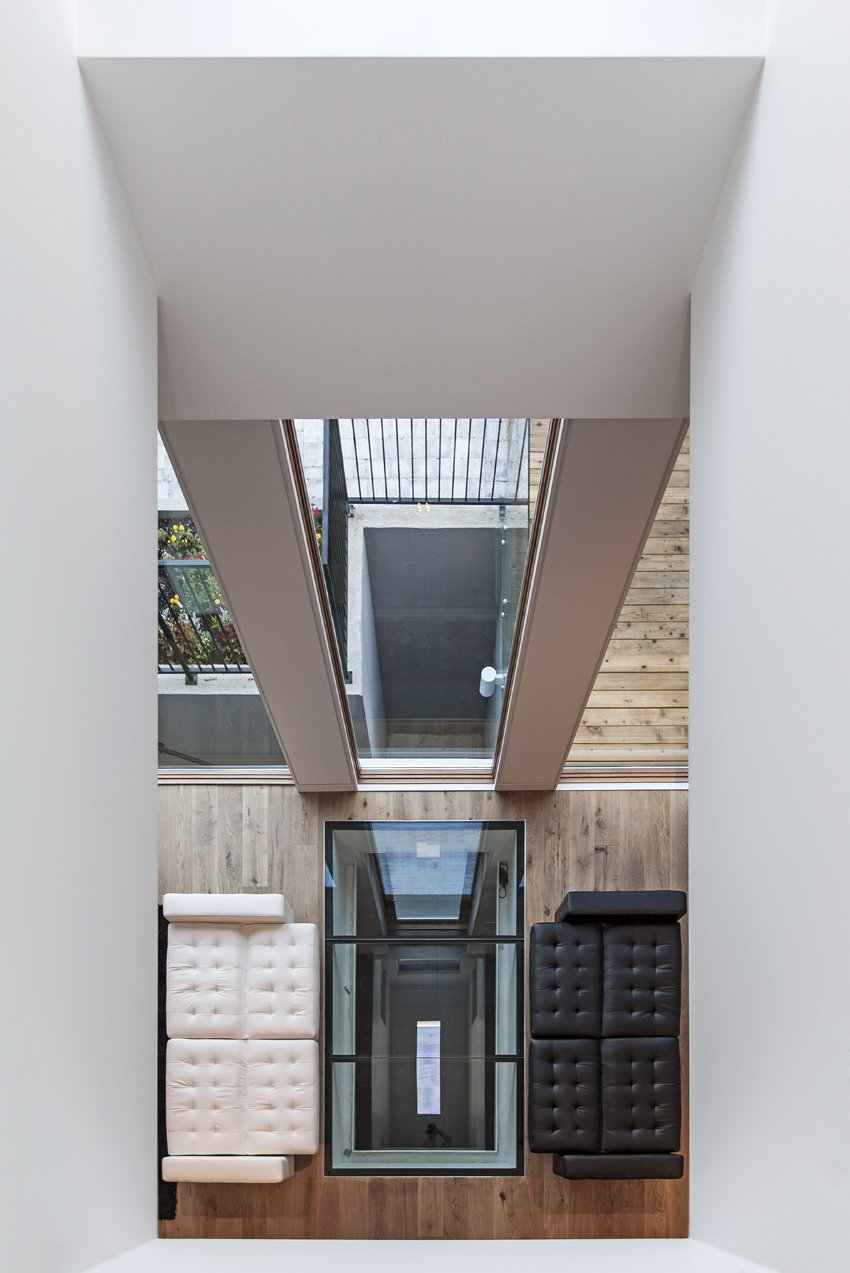 Looking downwards from the second floor, the void creates an invisible barrier between the family room and the living area. The reflection from the skylight exaggerates the idea of an even more depth within the house.  Photo 7 of 7 in Toronto's Tetris Inspired Home