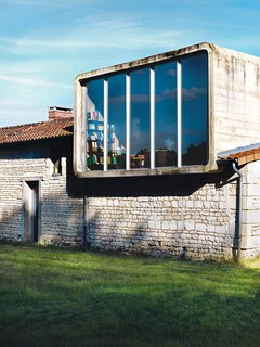 The second-floor office is housed inside a rounded rectangle of concrete that the architect inserted on top of the old farmhouse.