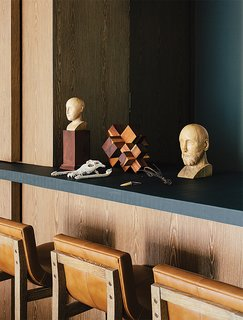 In the dining room, antique wooden busts and a machiche cross designed by Farca are arranged on a resin countertop by Monica Calderon. The bar conceals a service area with an espresso machine.