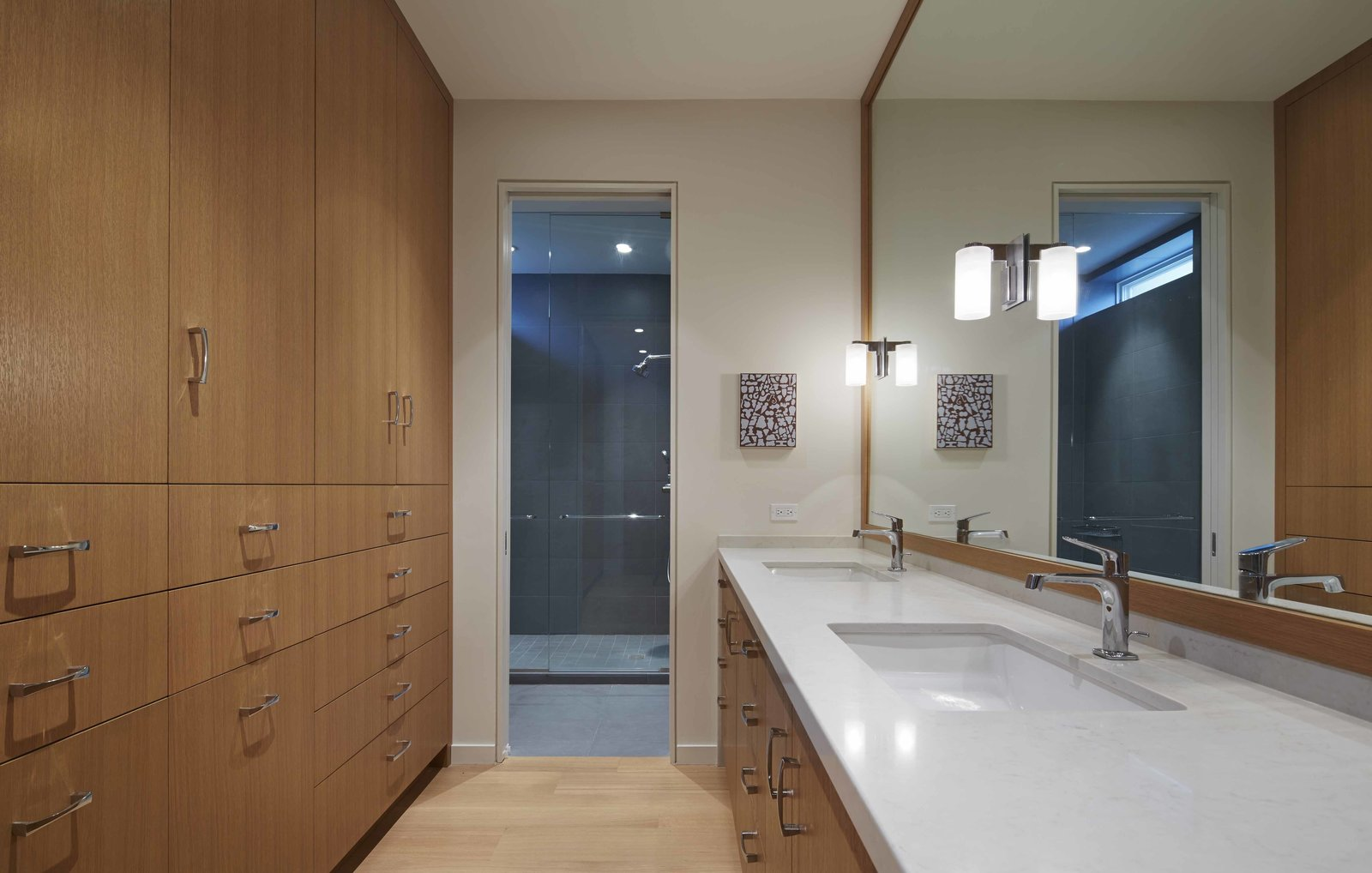 """The master bathroom strikes a balance between the desires of both parties. Warm wood cabinets and floors mingle with the darker glass and stone setup in the shower area. """"Although this was very much Lisa's addition, there was an understanding between the two that Bruce had to be part of it,"""" Valerio says.  Photo 6 of 6 in A Two-Story Addition Turned a Bachelor Pad Into a Comfortable Home For Two"""