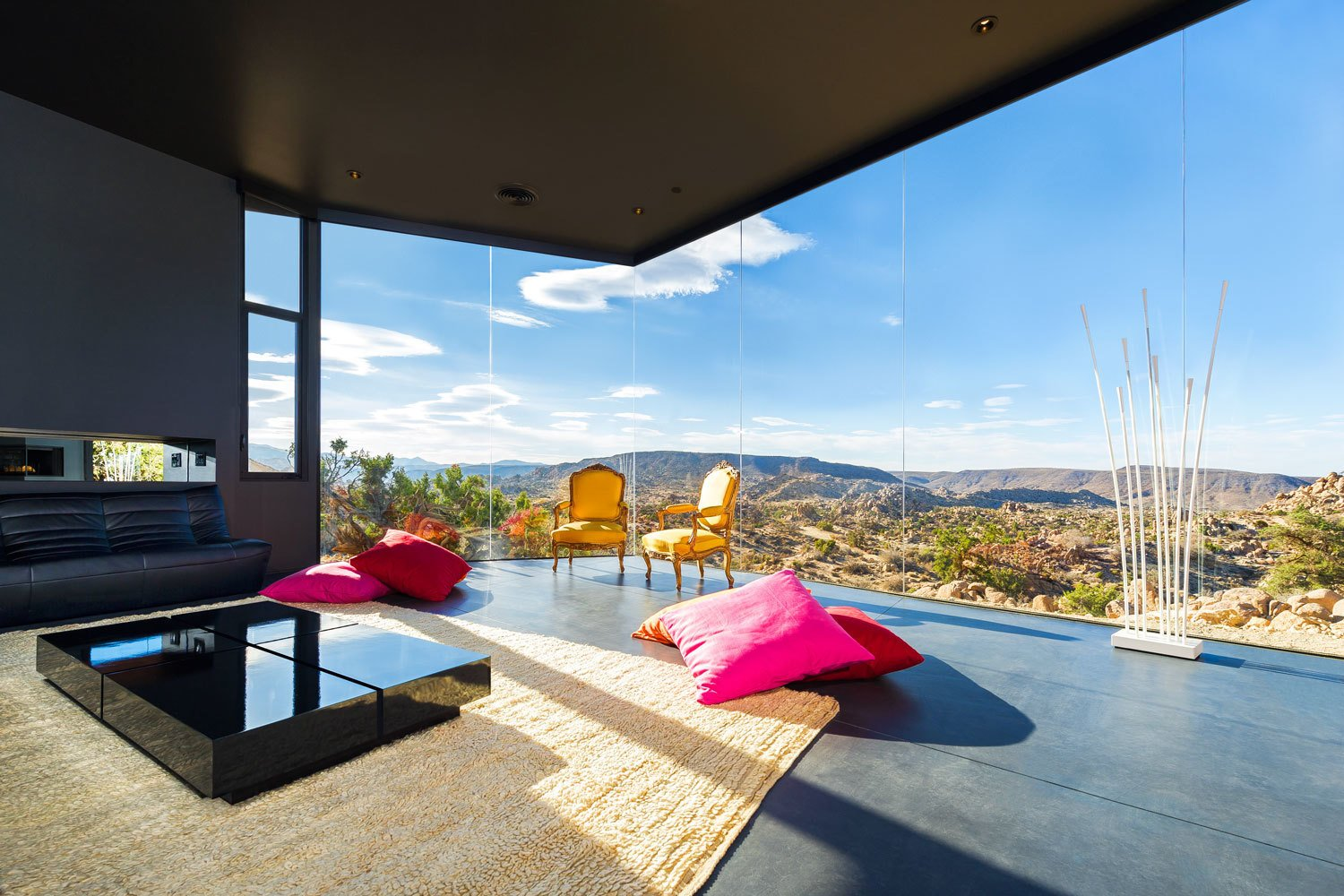 After sundown, the house itself seems to dematerialize into a dark starry expanse. For that reason, the homeowners have likened the living room to a campsite.  Photo 6 of 8 in A Sculptural Desert Escape Inspired by a Shadow