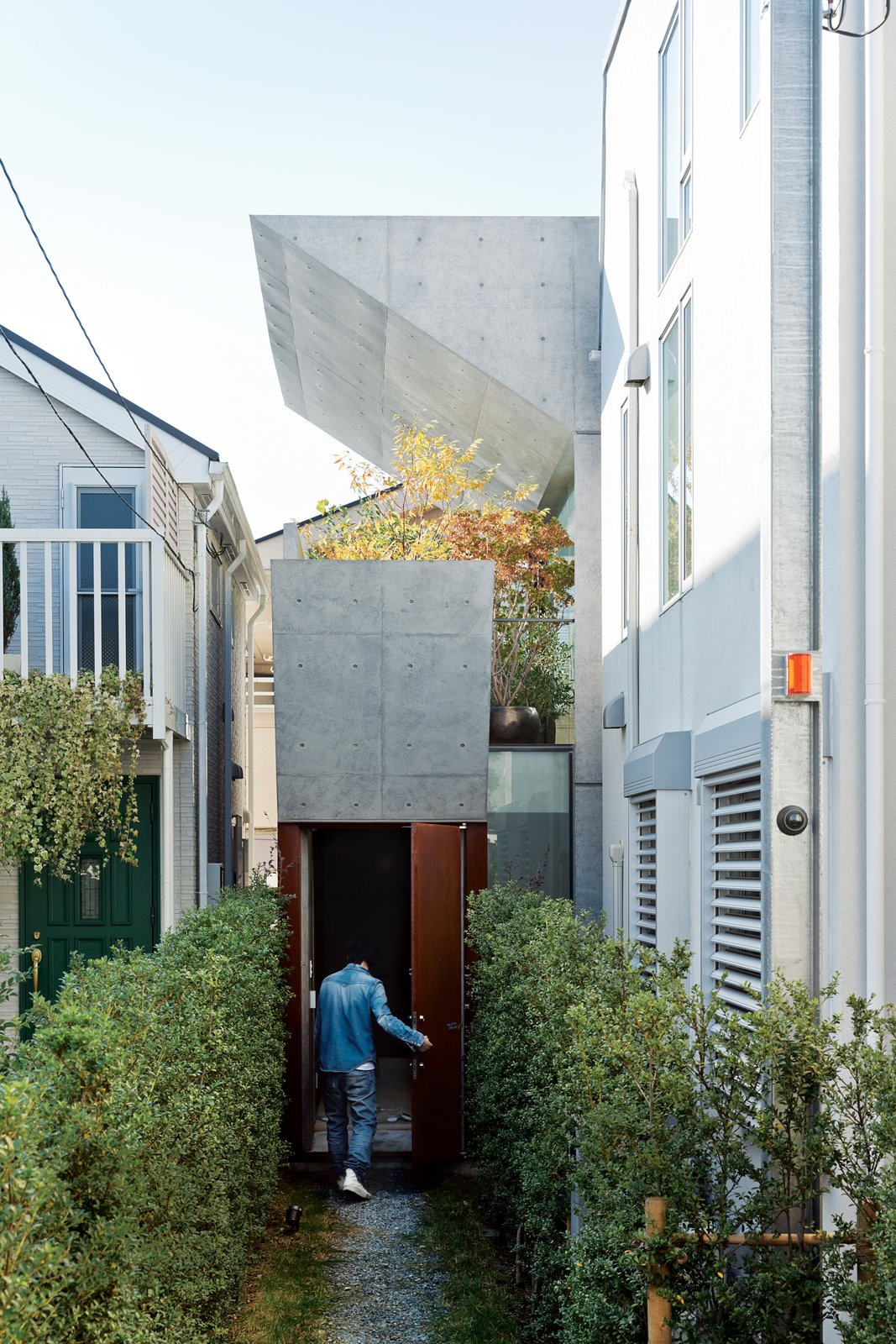 Outdoor, Walkways, Side Yard, Gardens, Shrubs, Front Yard, and Garden After purchasing a thin, L-shaped lot in Tokyo, Tamotsu Nakada asked architect and friend Koji Tsutsui to create an open-plan concrete home to fit the site.  Photo 1 of 7 in Open-Plan Concrete Home in Japan