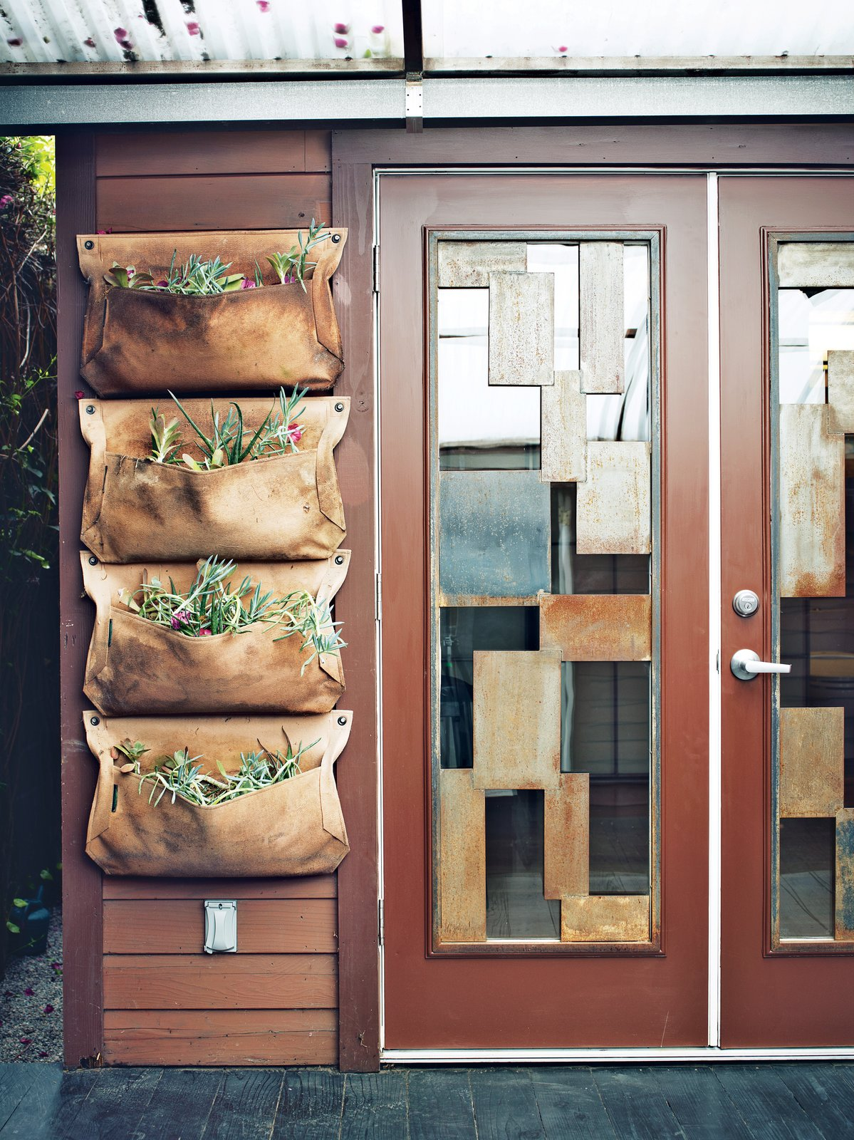 Doors, Metal, Swing Door Type, and Exterior The area includes a Wally planter from Woolly Pocket near the custom steel-and-glass doors.  Photo 13 of 13 in The Tiny Hollywood Home of Mad Men's Vincent Kartheiser