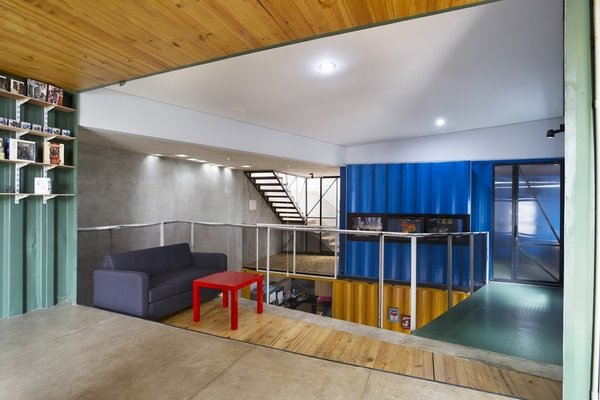 Natural light pours into the open-plan house, which is outfitted with low-cost materials like polished concrete floors and recycled metal railings.