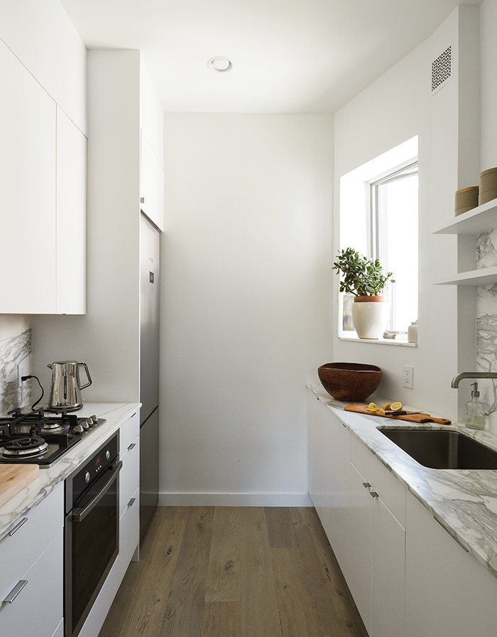 Kitchen, Refrigerator, Range, Undermount Sink, Marble Counter, Medium Hardwood Floor, and White Cabinet In the new space, small-scale, 24-inch appliances from Fagor are incorporated into Ikea's Applåd cabinetry.  Photo 12 of 14 in How One Family of Three Does It All in 675 Square Feet