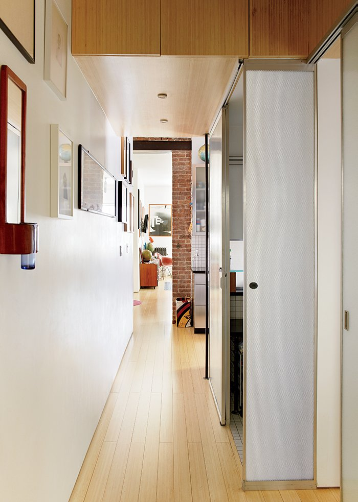 """Hallway and Light Hardwood Floor Encased in Panelite, the bathroom creates a lantern effect when illuminated from within. """"At night it's nice because you can put on the shower light, close that door, and it's like a floating box in the apartment,"""" McManus says. """"It just glows.""""  Photo 9 of 12 in Bright Renovation of a Tiny Manhattan Apartment"""