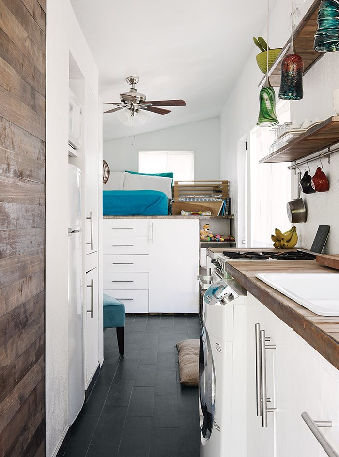 Laundry Room, Concealed, Wood Counter, and White Cabinet Porcelain floor tile from Daltile is a durable, easy-to-clean substitute for wood. The family does laundry in an efficient Summit SPWD1800 washer-dryer combination unit. Miller saved money in the kitchen by using a reclaimed sink and faucet and drawer pulls from Ikea.  Photo 4 of 4 in Tiny House Fits a Family in 196 Square Feet