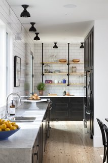 When beginning construction, Austin-based contractor Royce Flournoy hoped that the simple, gabled structure of the farmhouse-style home he now shares with his partner would blend seamlessly into the urban space around it. Flournoy's partner is a baker, and was given free reign to develop a kitchen that met his needs. The space combines black, Shaker-style cabinets, white subway tiles, Carrera marble countertops, and wooden floors to create a balance between rustic warmth and industrial simplicity.