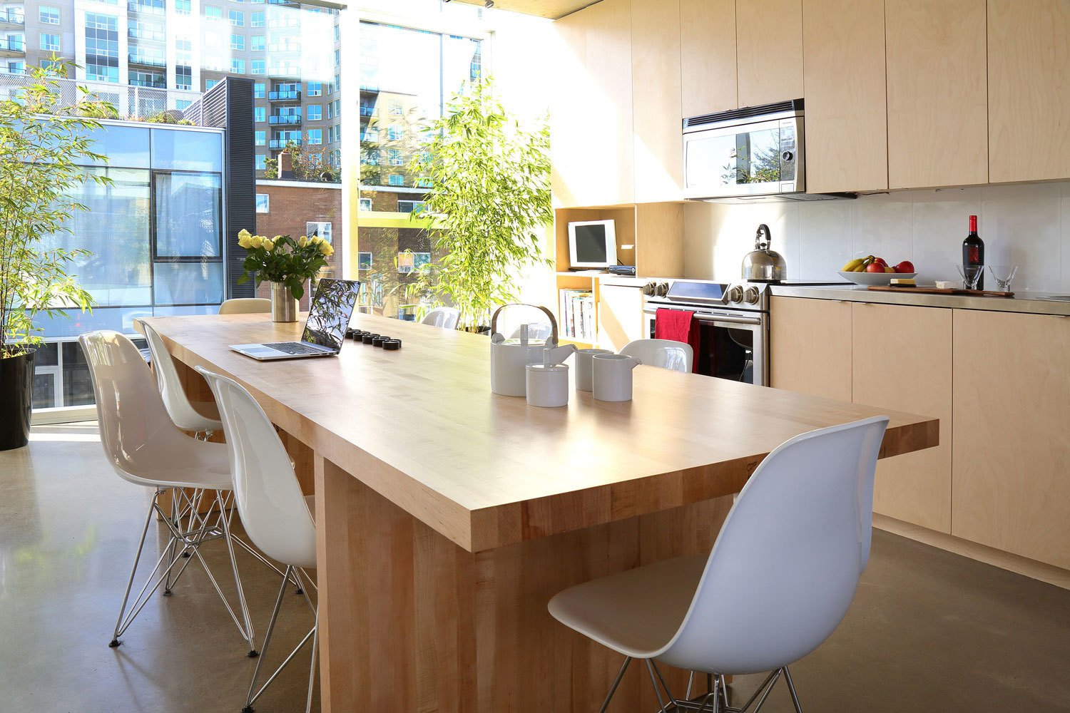Kitchen, Metal Counter, and Wood Cabinet The kitchen features stainless steel prep counters, a Samsung stove, and Panasonic over-the-range microwave. The room is bordered by two full walls of windows, allowing light to flood the space at all times of the day. A custom birch butcher block table furnishes the family gathering space.  Photo 8 of 9 in The Architect Next Door