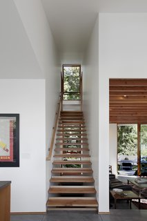 A small, efficient home in Seattle designed by SHED Architecture & Design incorporated wood on the exterior and interior of the home, and even used salvaged wood from the residence that had previously stood on the site. Although the 100-year-old bungalow was demolished, the treads of one of its staircases were repurposed in the new home as a modern, open-riser stair that lets in light from the windows beyond.