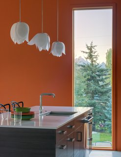 A Fun, Cost-Conscious Home With Bright Interiors and a Climbing Wall - Photo 4 of 9 - A polished chrome faucet from Kohler's Purist collection enhances the kitchen. Walls and ceilings are made of drywall and painted brilliant hues that complement the home's industrial exterior.