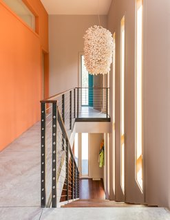 """A Fun, Cost-Conscious Home With Bright Interiors and a Climbing Wall - Photo 6 of 9 - A Cascade suspension light by Ango hangs over the stairway. Extra-thick, exposed concrete floors contribute to the home's radiant heating and cooling system. """"There's more upfront cost, but because Jackson's heating season is so long, it's actually a very economical choice,"""" Logan says."""