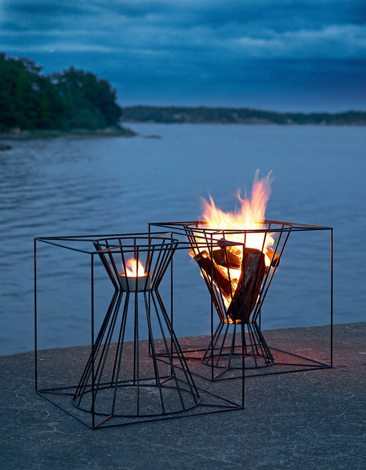 Outdoor The Boo Fire Basket from Skargaarden is made of black lacquered steel. Designed to fit several logs for an outdoor fire, the Boo can also be overturned to hold a candle or lantern.  Photo 3 of 8 in Gather Around These 7 Modern Fire Pit Designs from Modern Fire Baskets for Late Summer Evenings