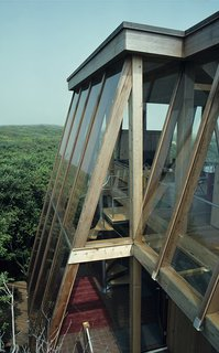 "Few architects changed the face of Fire Island as much as the midcentury master Horace Gifford. In 1975, he created this geometric glass ""tree house"" on Sail Walk, which sports screened vents between slanted glass walls and suspended floors that draw breezes through a chimney-like skylight."