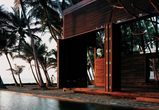"""It's hard to believe that this idyllic house sited in a coastal coconut grove in Nandgaon, India, is a mere hour's drive from bustling Mumbai. For architect Bijoy Jain, principal at Studio Mumbai Architects, making the most of the muggy locale meant foregoing walls for louvers and slatted sliding doors—and opting for local materials to construct the airy home. """"Response to weathering is critical along the seaside,"""" he explains. The East Indian laurel, Burma teak, and palmyra woods will endure the seaside climate with an oiling after each monsoon. The pool that runs between the two structures of the home contrasts the choppy white-capped ocean with tranquil charm, making it a favorite spot for the vacationing family of four, who spend weekends here at the retreat."""