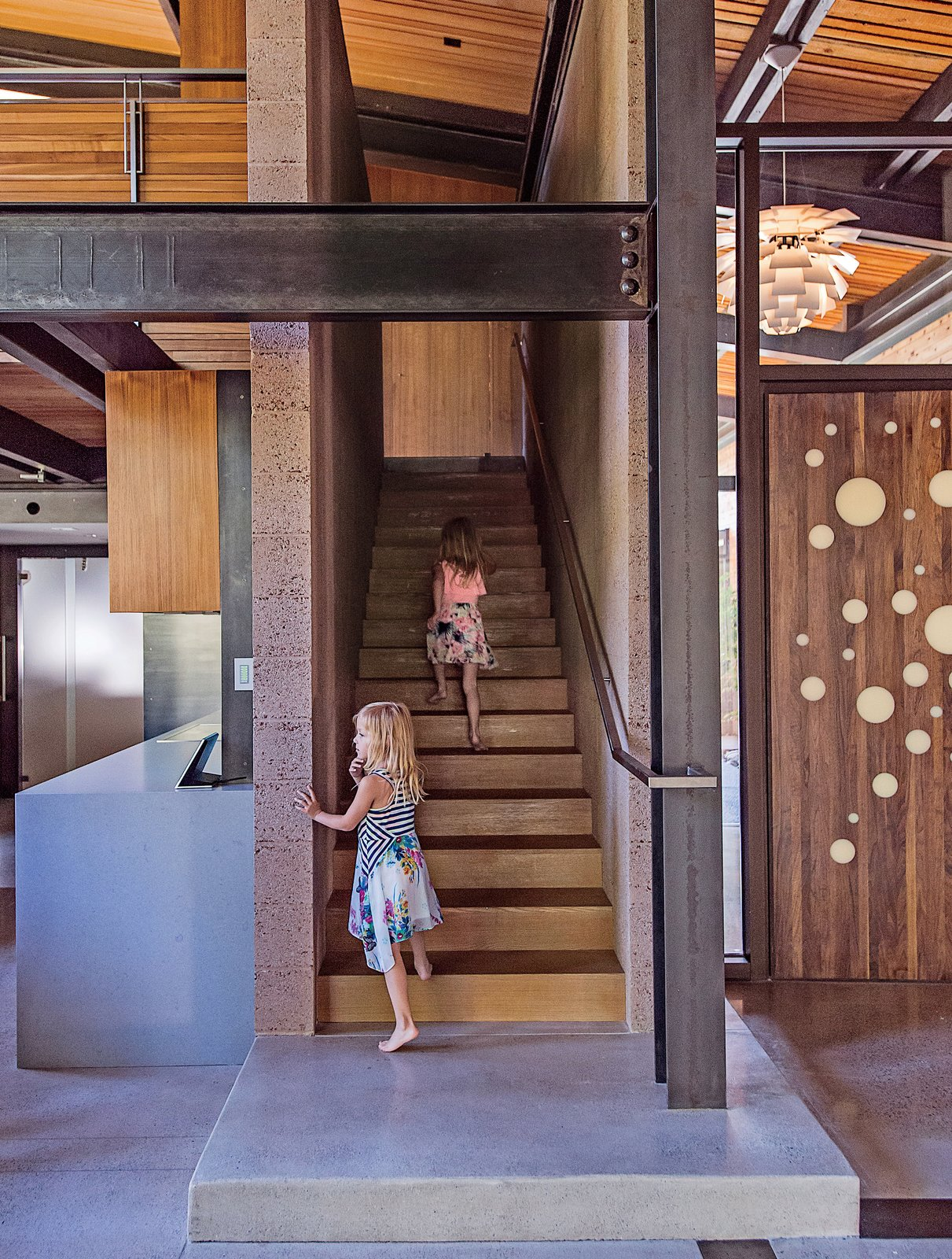 Staircase, Metal Railing, and Wood Tread The entrance is highlighted by a custom walnut door designed by the architect, Jack Hawkins. Cheryl Chenault designed the interiors.  Photo 2 of 19 in A Forest Sanctuary Designed to Support Autistic Triplets, Their Parents, and a Host of Caregivers