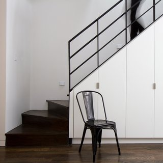 In a Brooklyn home renovated by Office of Architecture, subtle details on bright white cabinets keep this space under the stairs from feeling anything but dark and dreary, despite the dark wood treads and risers and black iron handrail. Thoughtful details, like simple, geometric hardware and hidden hinges, keep this often-awkward space useful and appealing.