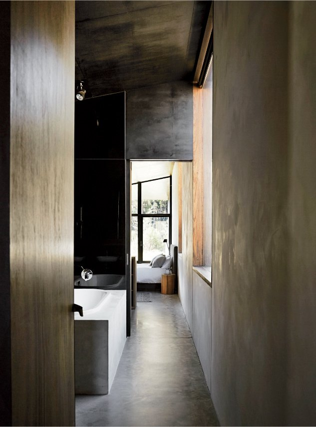 Hallway and Concrete Floor Dulux Ferrodor 810 industrial paint in Mid Grey, dark formply timber ceiling cladding, and concrete floors give the interiors a brooding intensity.  Photo 3 of 10 in Richly Furnished Home Frames Striking Landscape Views