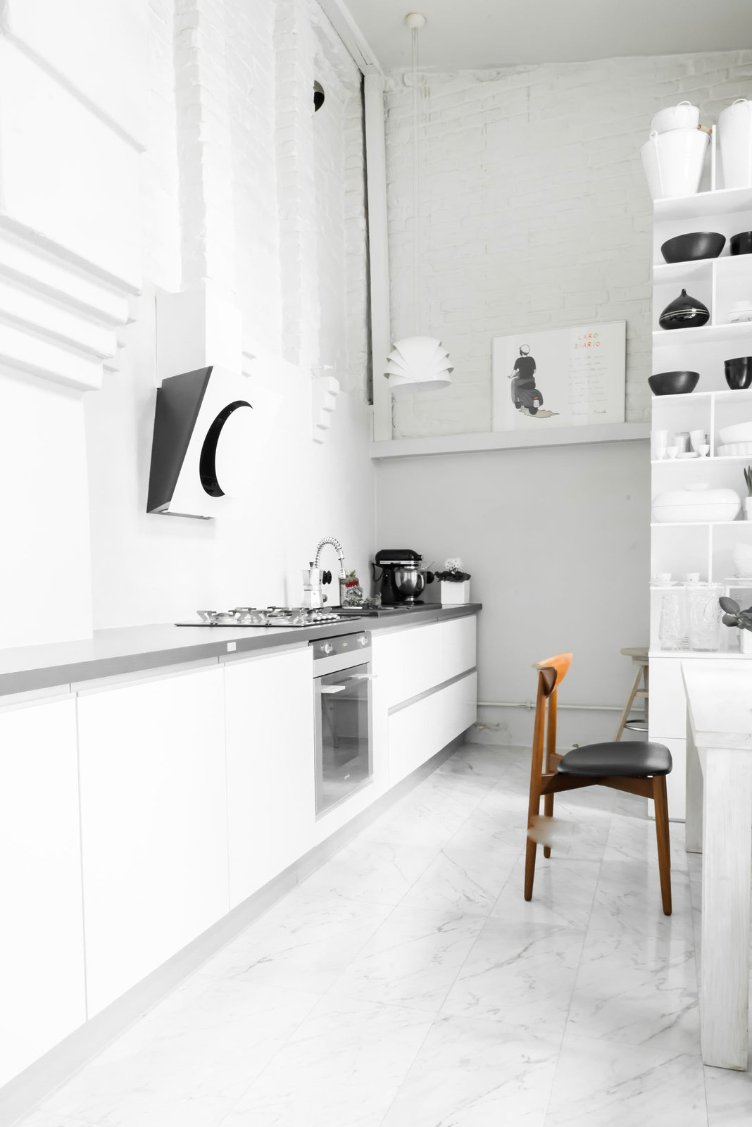 "Kitchen, White Cabinet, and Marble Floor In the kitchen, an exposed brick wall stands out against the milky smoothness of the marble tile floors. ""I wanted the house to be raw and interesting,"" Kolasiński explains. The large cupboard was designed by his company. Appliances are by Smeg and the stove hood is by Elica.  Photo 7 of 10 in A Run-Down Farmhouse Becomes a Sleek Modern Retreat"