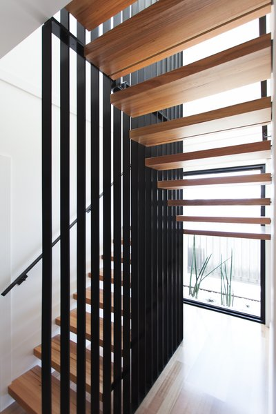 A striking stair defines the entry to the house; it features minimalist floating timber stair treads wrapped around a woven steel mesh blade wall.