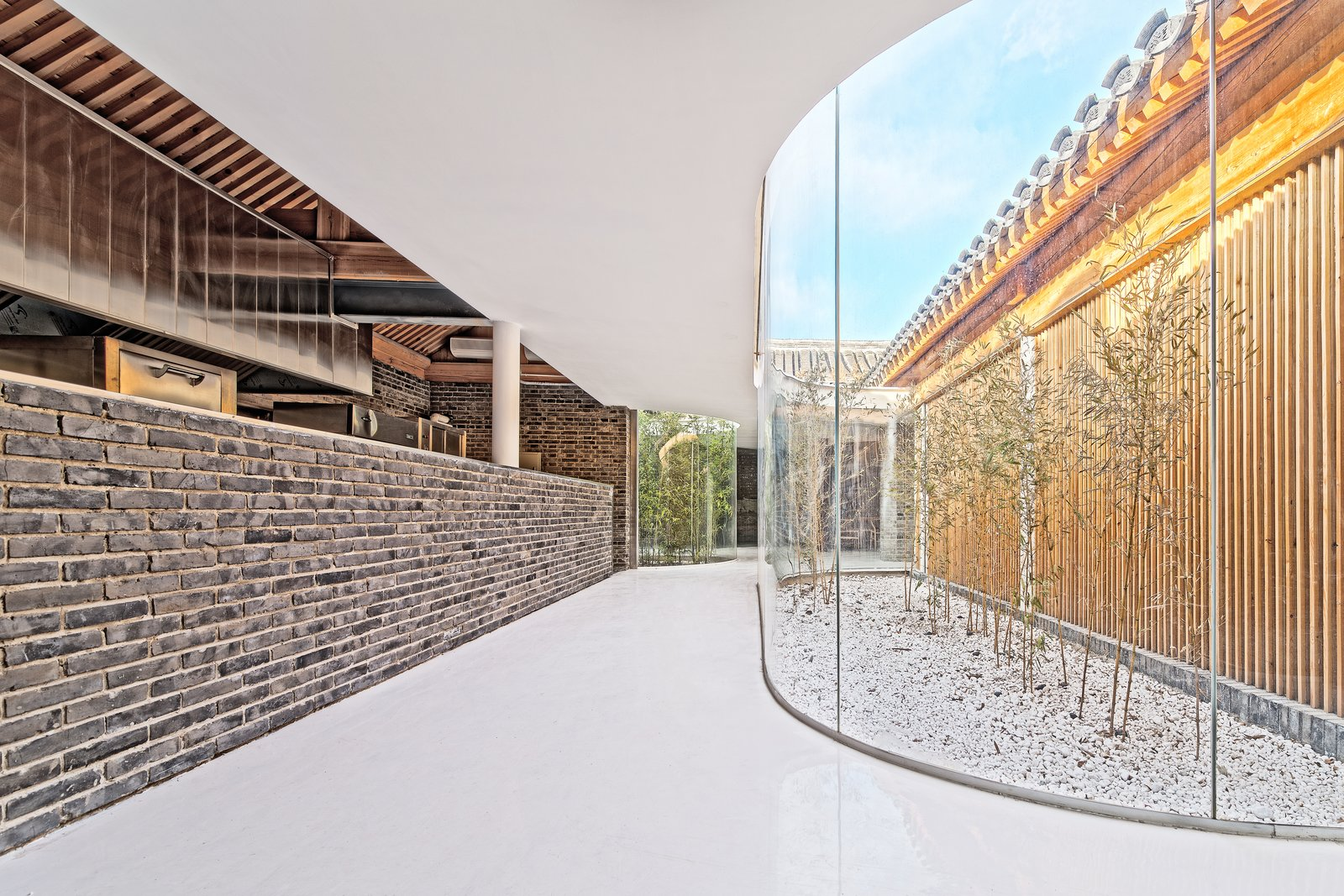 To ensure modern temperature control, the building had to be enclosed. The architects installed transparent glass walls to create a constant visual connection to the building's historic features.  Photo 3 of 7 in An Historic Beijing Structure Gets a Modern Makeover