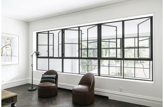"""""""We did a lot of studies for the project to show how we could get huge amounts of light into the rear of the house,"""" Roberts said, which culminates in the two-story addition that replaced the original collapsing wall. The living room's two antique round leather chairs, by Ralph Lauren, are within view of the garden beyond matching sets of windows."""